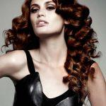 Long curly hair with dark red copper tones
