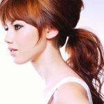 Teased light and dark copper hairstyle with teased ponytail and bangs